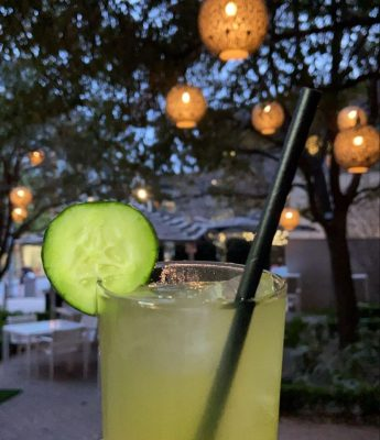 a margarita with a cucumber garnish is in front of large outdoor lights hanging from trees on a patio with  outdoor umbrellas over the tables