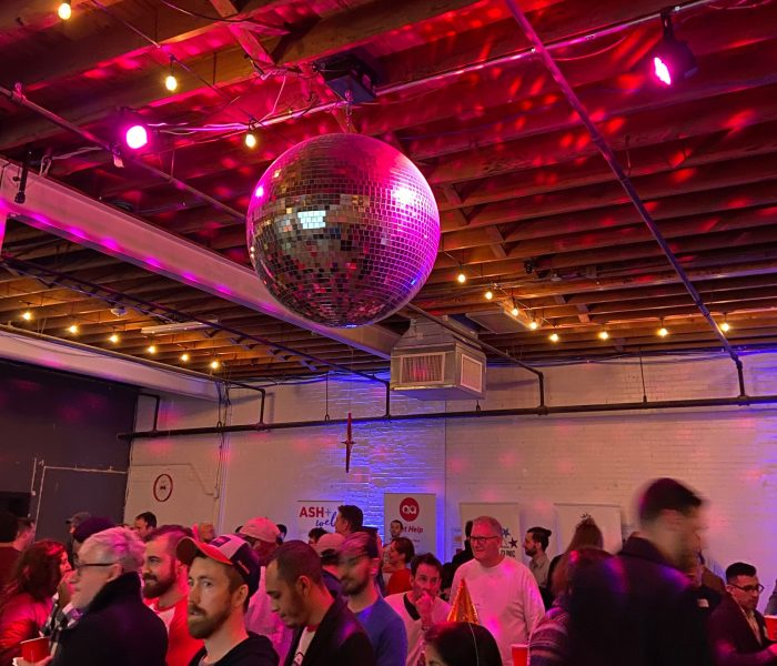 pre-pandemic party scene with a lot of people in a room and a big disco ball on the ceiling